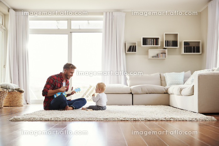 Father playing ukulele with young son in their sitting roomの販売画像