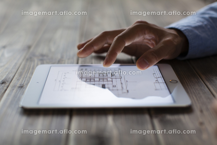 タブレット型PCで家の設計図面を見る男性の販売画像