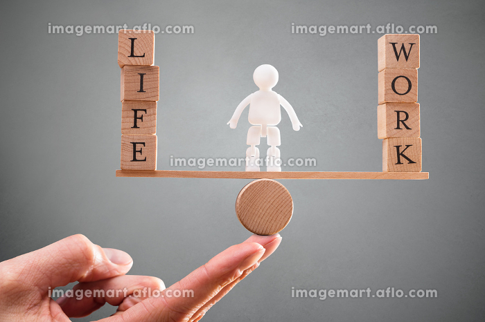 Person's Hand With Work And Life Wooden Blocks On Seesawの販売画像