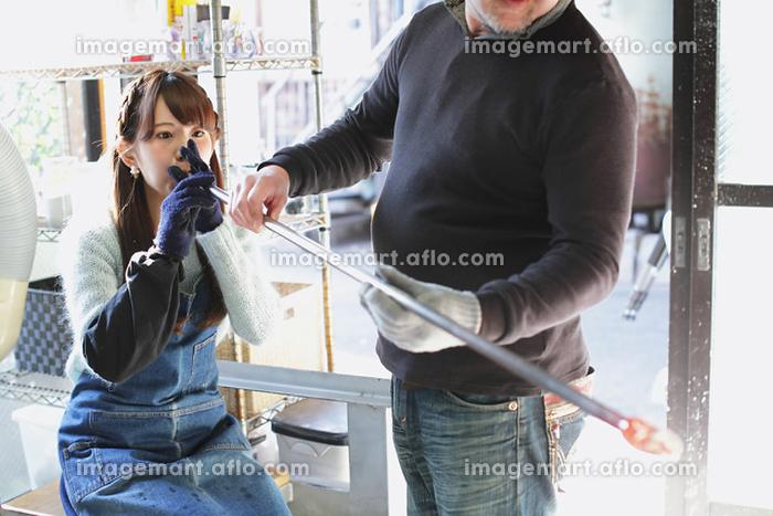 吹きガラスを体験する女性
