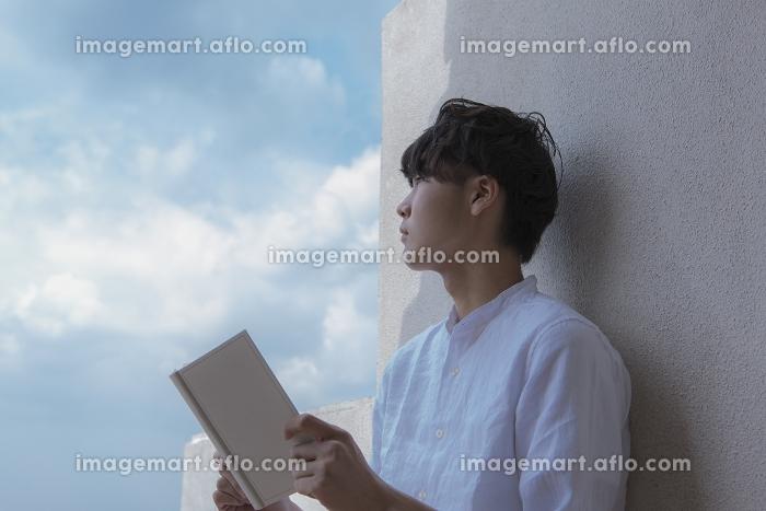 青空の下で本を開く日本人男性