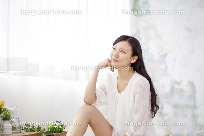 窓辺でくつろぐ女性の販売画像