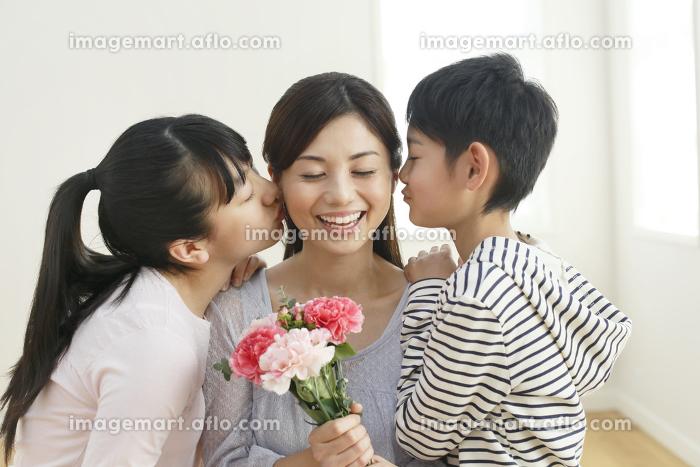 花束を持つお母さんにキスをする子どもたちの販売画像