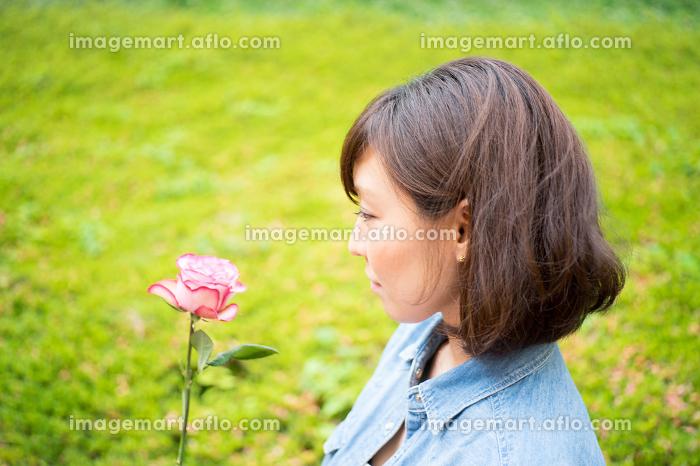 一輪のバラを持つ女性の販売画像