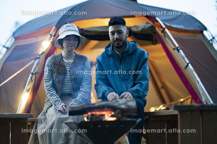 暗がりの中、焚き火を楽しむ男女の販売画像