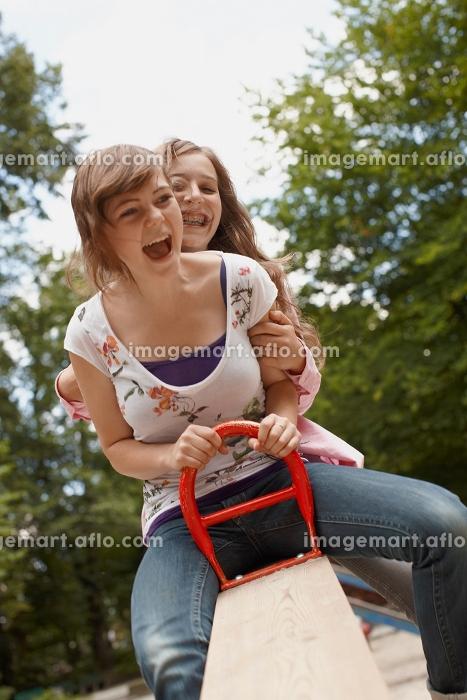 2 girls having fun together in a parkの販売画像