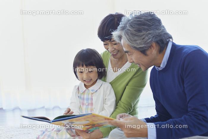 孫と絵本を見る祖父母の販売画像