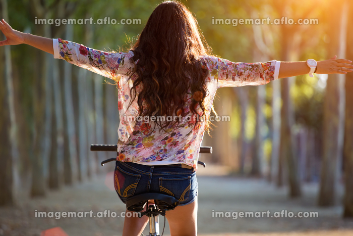 Pretty young girl riding bike in a forest.の販売画像