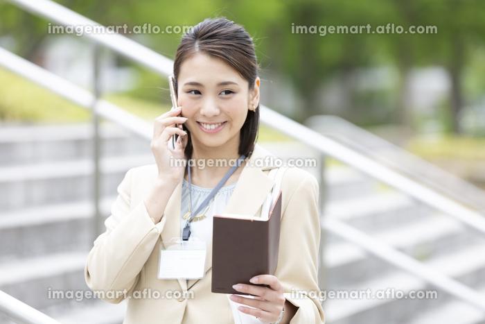 電話をする日本人のビジネス女性の販売画像