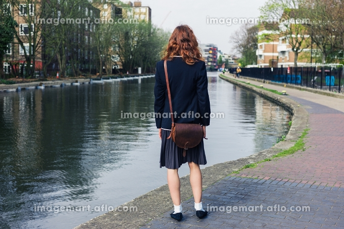 A young woman wearing a skirt and a jacket is standing by a canal in the springの販売画像