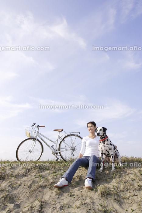 サイクリングの途中で愛犬と休憩する女性の販売画像