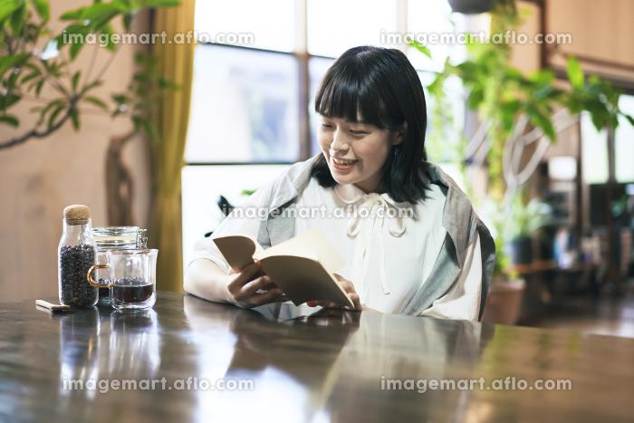 暖かい雰囲気の空間で、本を読む若い女性の販売画像