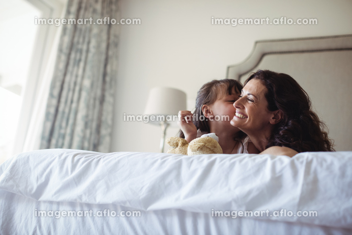 Daughter kissing her mother on cheek in bedroom