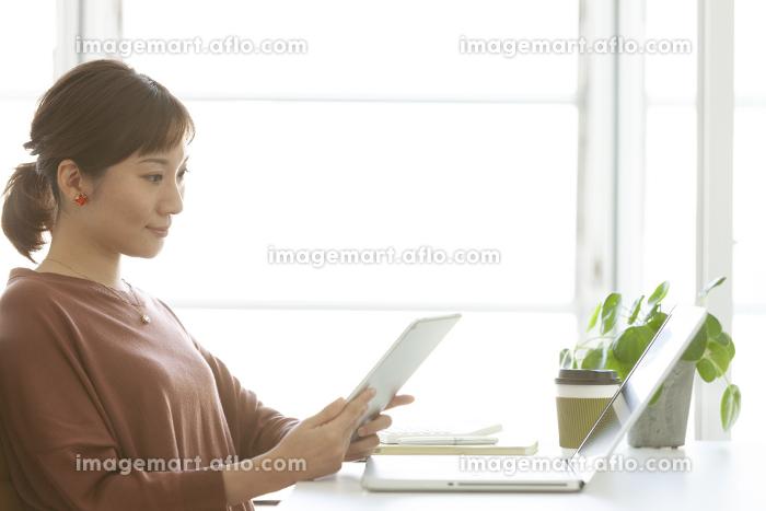 タブレットPCを見ているビジネスウーマンの販売画像