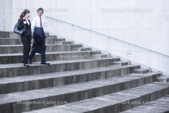 階段を下るビジネスマンとビジネスウーマン
