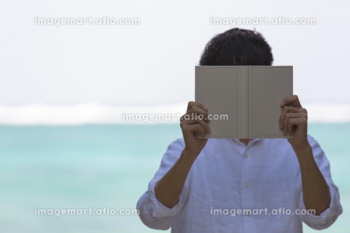 本で顔を隠す日本人男性の販売画像
