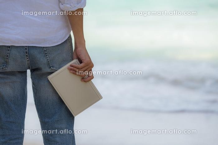 海辺で本を持つ男性の販売画像