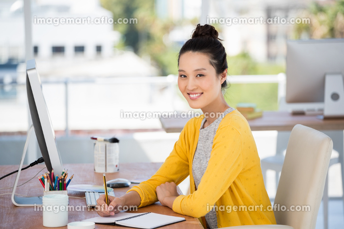 A woman is working at her deskの販売画像