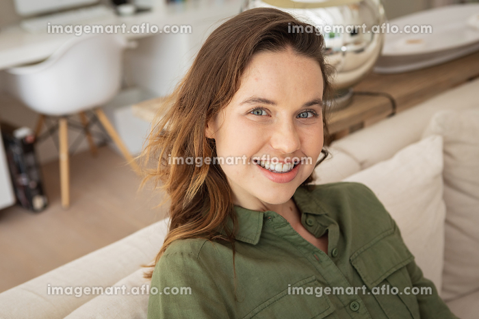 Portrait of a happy, attractive Caucasian woman spending time at home, sitting on sofa. Lifestyle at home isolating, social distancing in quarantine lockdown during coronavirus covid 19 pandemic.の販売画像