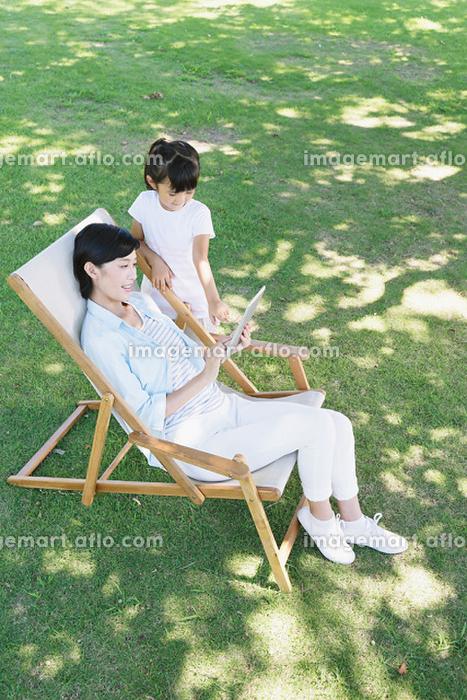デッキチェアでくつろぐ母親と娘