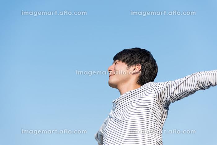 青空の下でリラックスする若い男性の販売画像