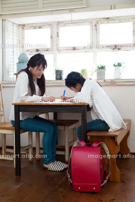 勉強する娘とそれを見る母親の販売画像
