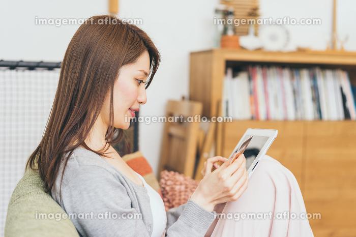 ソファでくつろぎながらネットショッピングを楽しむ女性の販売画像
