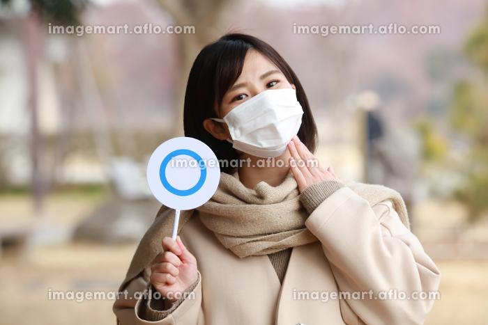 マスクを着け〇札を持つ女性の販売画像