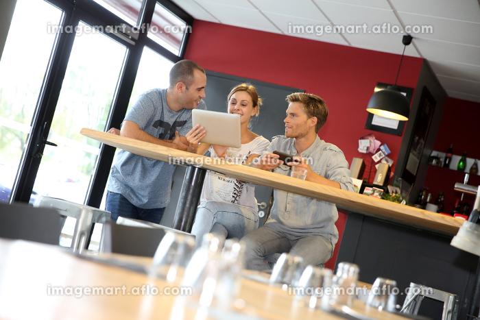 Friends in bar websurfing on tabletの販売画像