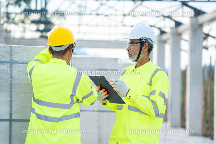 Civil engineer checking work with clipboard in progress of constの販売画像