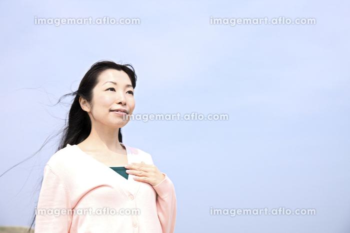 胸に手をあてる女性の販売画像