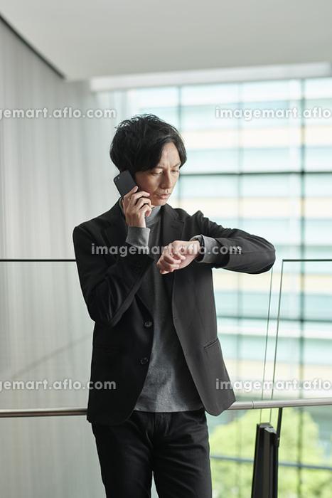 電話をしながら腕時計を見る日本人ビジネスマン
