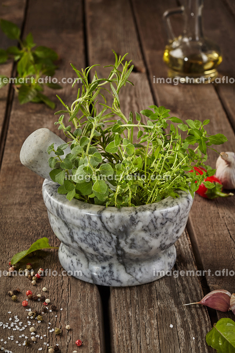 Fragrant herbs in mortar on wooden table with condiments and oilの販売画像
