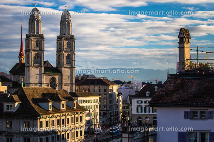 Zurich, Switzerland - view of the Grossmunster church with beautiful mountains in the backgroundの販売画像