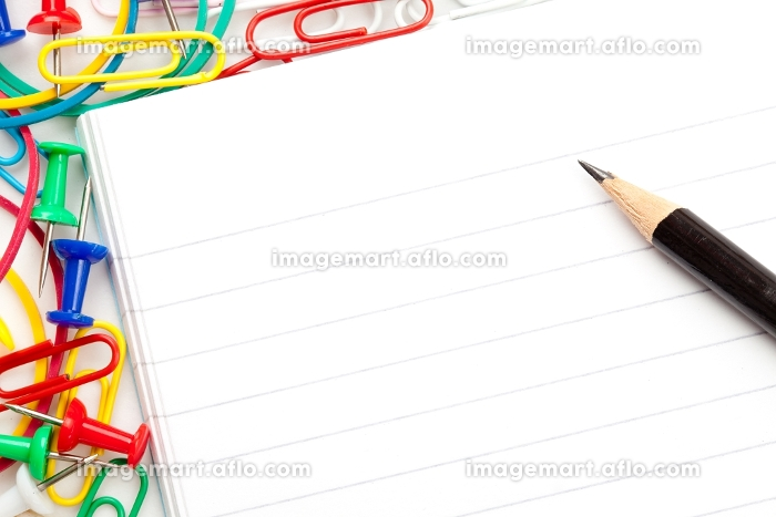 Notepad with large group of muti coloured stationery and a pencil against a white backgroundの販売画像