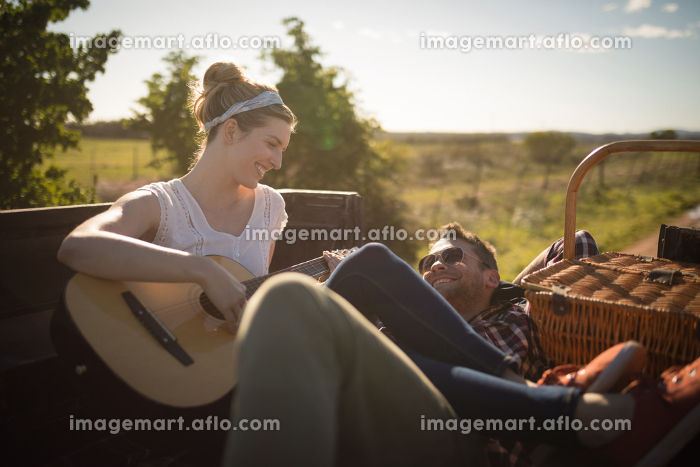 Woman playing guitar while man listening in a carの販売画像