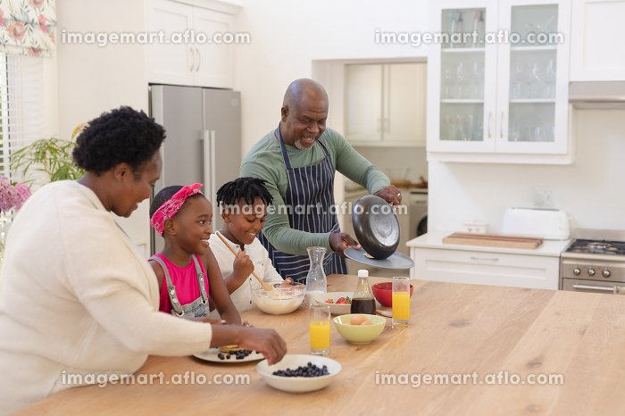 African american grandparents cooking with smiling grandson and granddaughter in kitchen. family spending quality time together.の販売画像