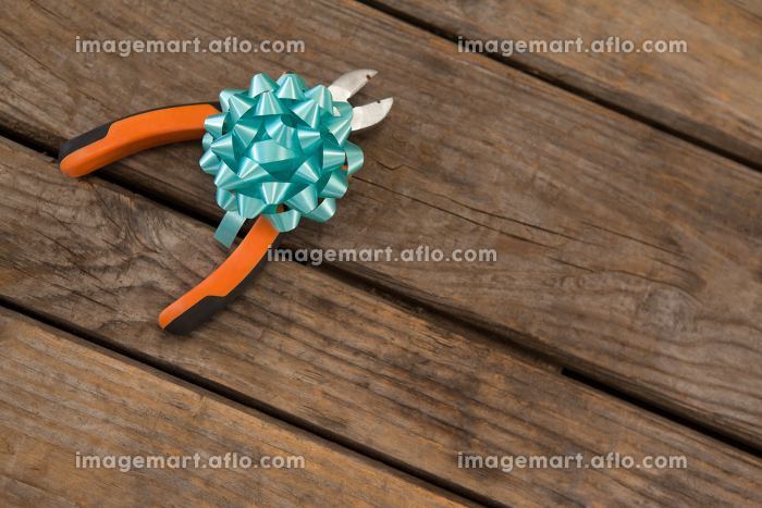 Ribbon with pliers on wooden table