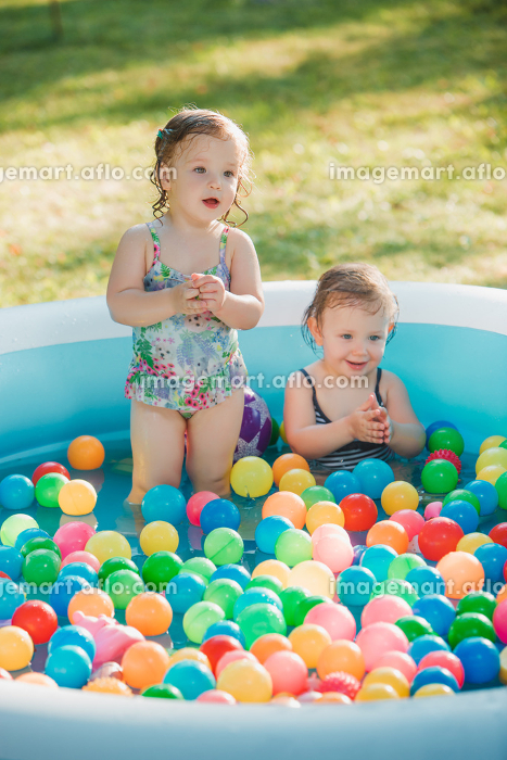 The two little baby girls playing with toys in inflatable pool in the summer sunny dayの販売画像