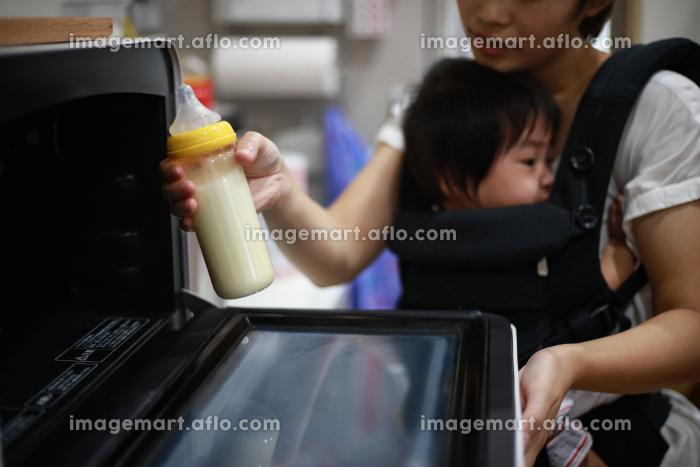 電子レンジでミルクを温めようとする母親の販売画像