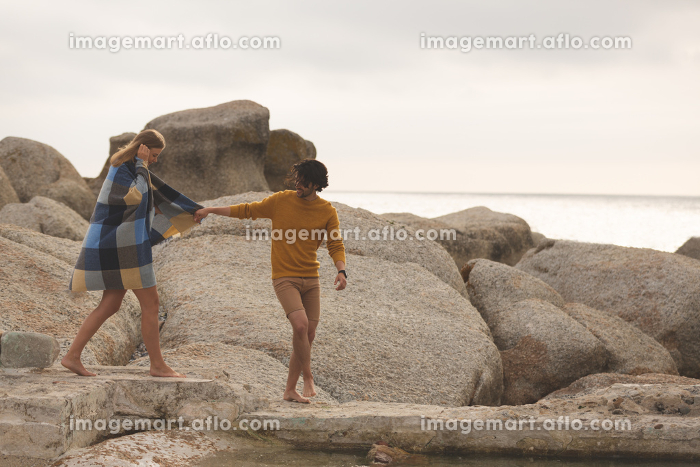 Front view of young Caucasian couple walking hand in hand on rock near beachの販売画像
