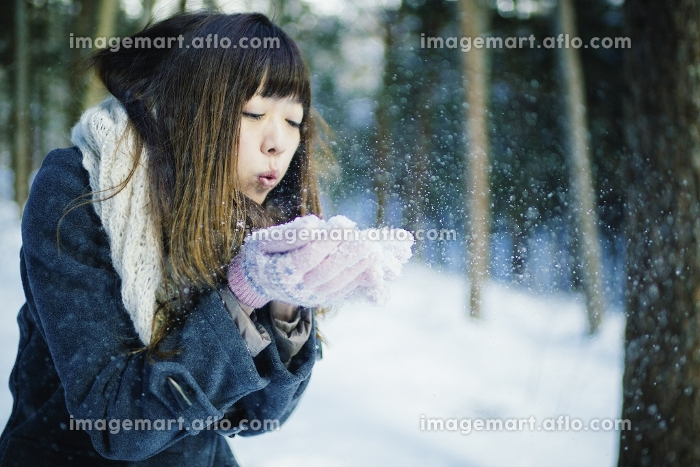 雪に息を吹きかけて飛ばす日本人女性の販売画像