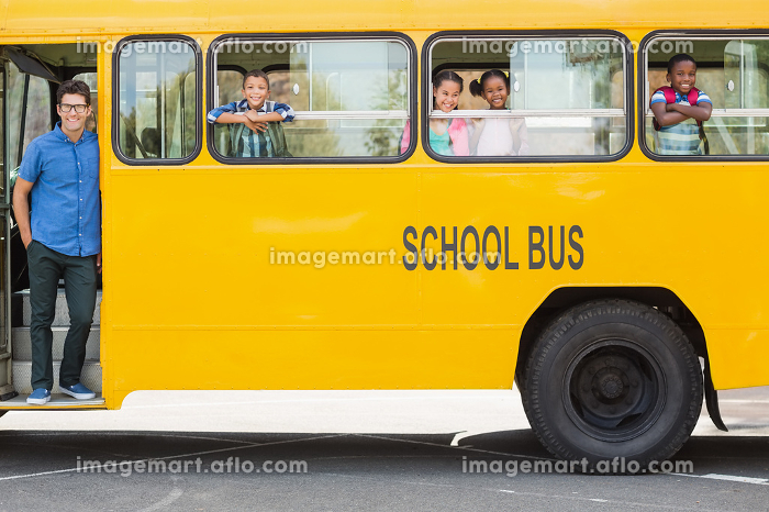 Portrait of teacher and kids looking from bus