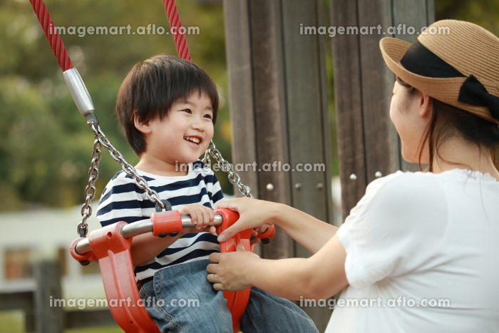 ブランコで遊ぶ親子の販売画像