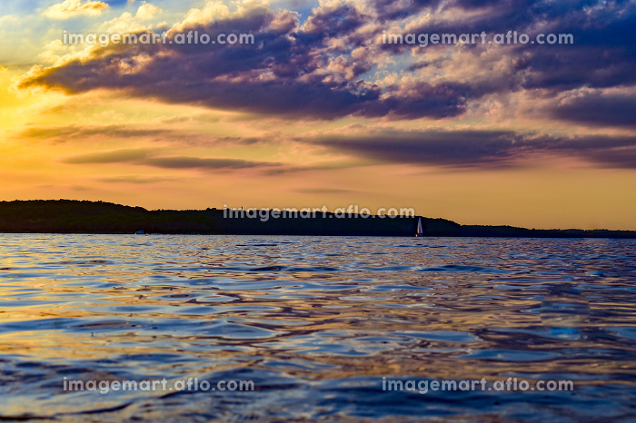 A small sailboat in front of a stunning sunsetの販売画像