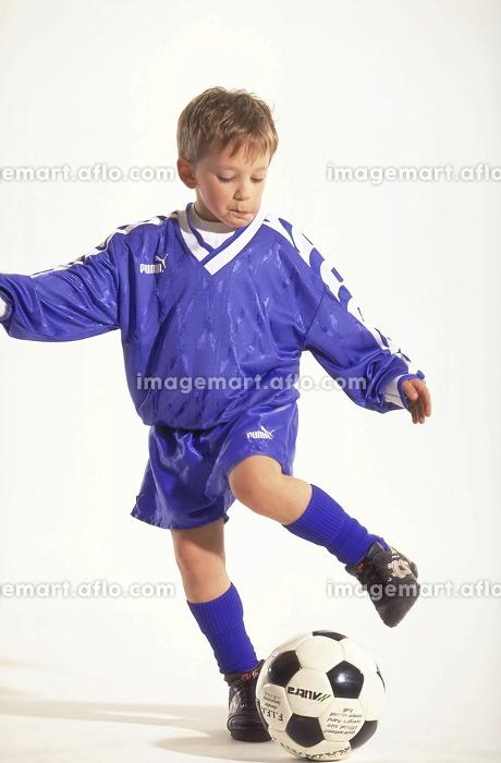 Portrait, Ganzfigur, Junge mit kurzen Haaren, Fussballer, 8 Jahre, bekleidet mit blauem Trikot und Stutzen beim Tribbeln mit dem Ballの販売画像