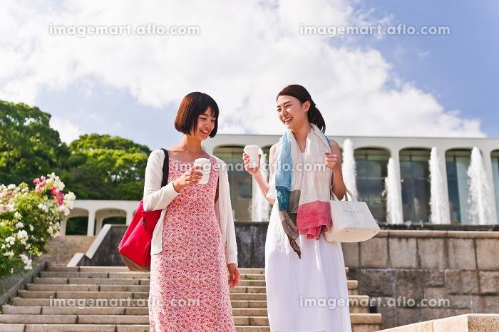 カップを片手に会話する女性