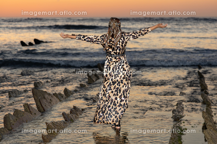 A young girl in a floral dress in the water on a sunset , Deba, PV, Spainの販売画像