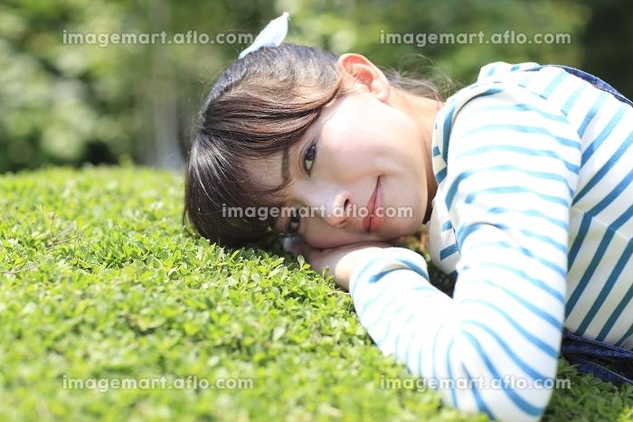 庭に寝転び寛ぐ女性の販売画像