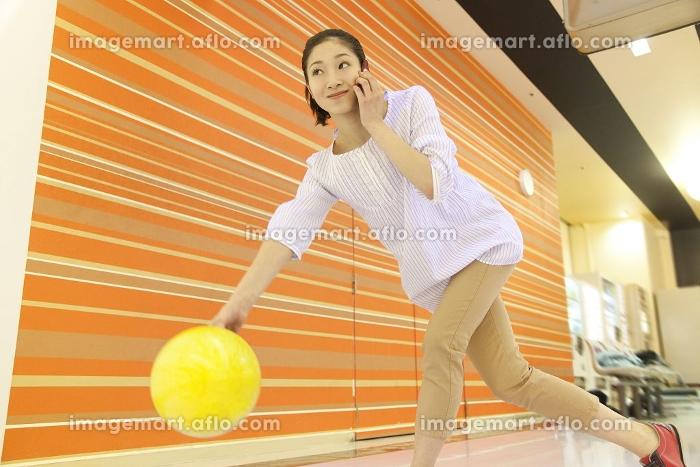ボウリングしながら電話する女性の販売画像